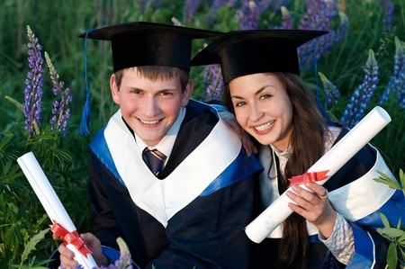 Two happy graduate students in gown and diploma sitting outdoors at sunset light photo