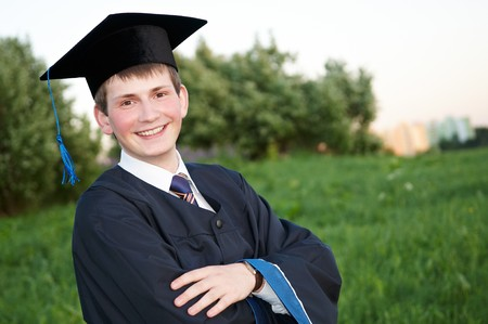 high school graduation: Young smiley graduate student in gown standing outdoors