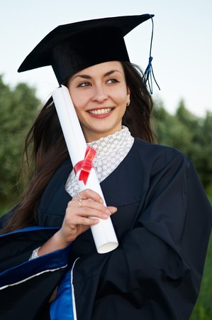 Young smiley graduate girl student in gown with diploma outdoors photo