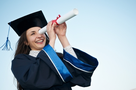 Young laughing graduate girl student in gown looking through diploma outdoors photo