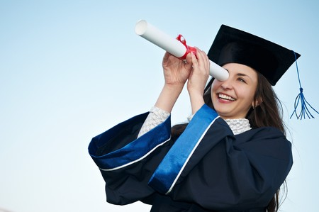 high school graduation: Young laughing graduate girl student in gown looking through diploma outdoors