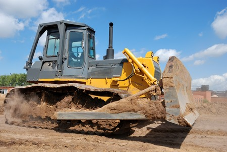 heavy equipment: Bulldozer loader at earthmoving works over brigt sky
