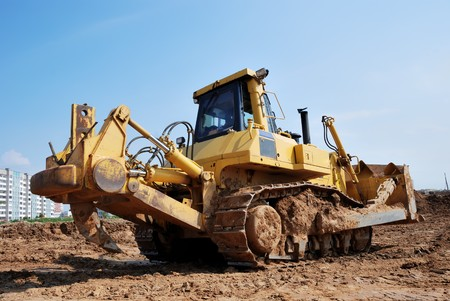 brigt: Bulldozer loader at earthmoving works over brigt sky with heavy ripper