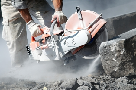 works: construction work of stone cutting by cut-off saw with diamond wheel Stock Photo