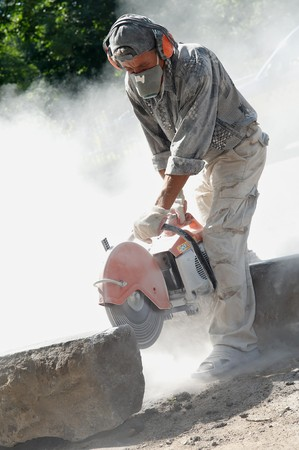 construction worker at stone cutting work by cut-off saw with diamond wheel photo