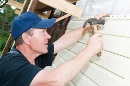 house renovation: Worker planking house with plastic siding panels Stock Photo