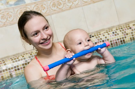 Mother and baby child in a swimming pool. Focus on baby face with mother defocused in the background. photo