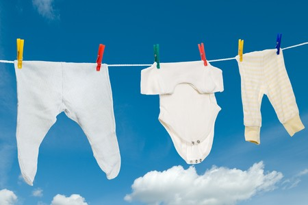 Baby clothing hanging on a rope with motley clothes pegs photo