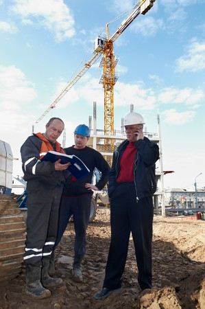 foremaster: Group of builders workers at construction site examining task documentation