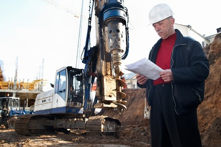 foremaster: builder inspector worker at construction site with documentation