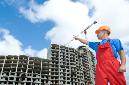 building construction: engineer worker directing up with finger to building under construction