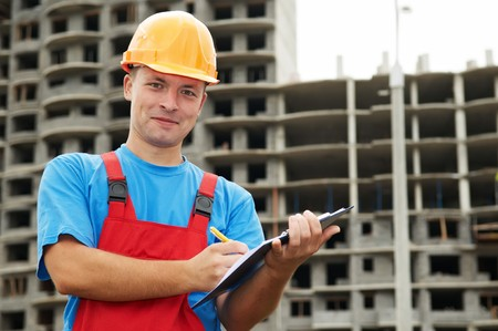 taskmaster: One happy builder worker with clipboard inspecting construction site Stock Photo