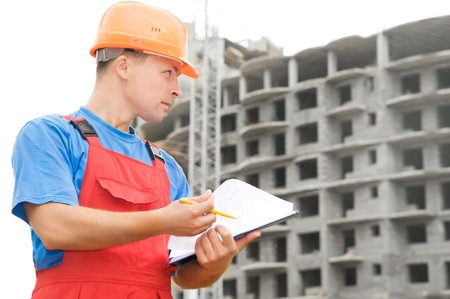foremaster: One builder worker with clipboard inspecting works at construction site