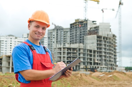 taskmaster: One happy builder worker with clipboard inspecting works at construction site