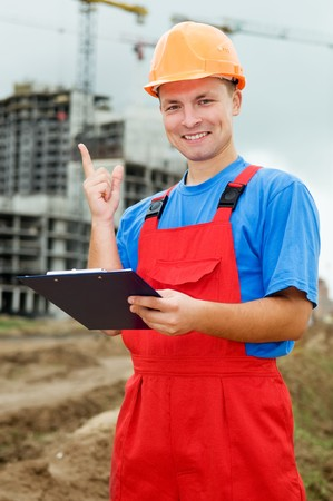 One smiley builder worker with clipboard and finger pointing up at construction site photo