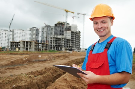 One happy builder worker with clipboard inspecting works at construction site photo
