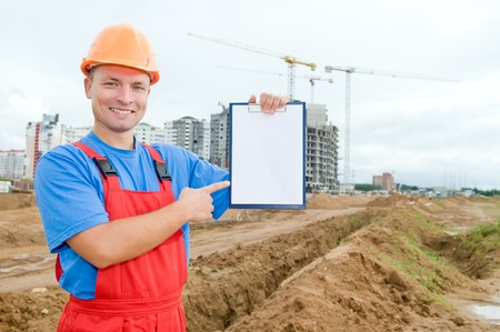 One smiley builder worker pointing the finger to clipboard over construction site photo