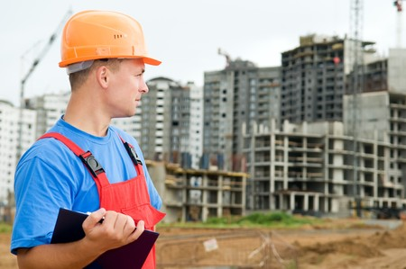 taskmaster: One builder worker with clipboard inspecting works at construction site