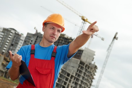 engineer builder at construction site directing up with finger photo