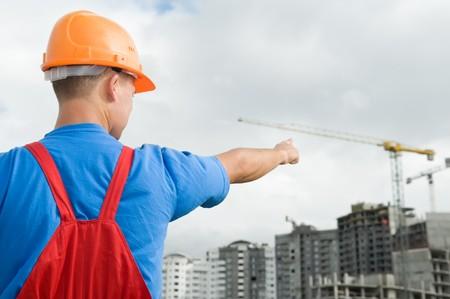Engineer Worker Regie mit Finger auf Gebäude im Bau