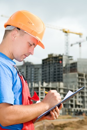 One builder worker writing in clipboard inspecting works at construction site photo