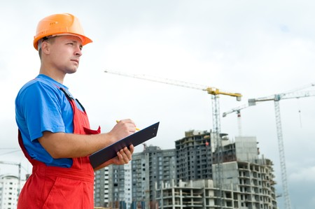 One builder worker with clipboard inspecting works at construction site photo
