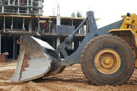 grading: vista de primer plano de una pala de cargador de rueda en el movimiento de tierras de construcci�n de obras