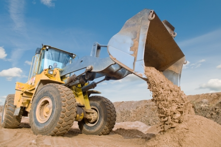 mover: Wheel loader machine unloading sand at eathmoving works in construction site