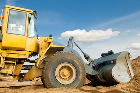 Wheel loader machine loading sand at eathmoving works in construction site over blue sky Stock Photo - 7565336