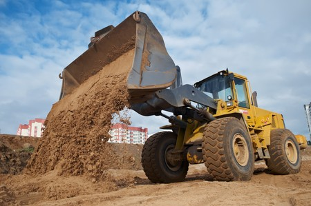 Wheel loader machine unloading sand at eathmoving works in construction site photo