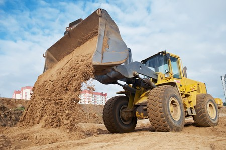 Wheel loader machine unloading sand at eathmoving works in construction site Stock Photo - 7565299