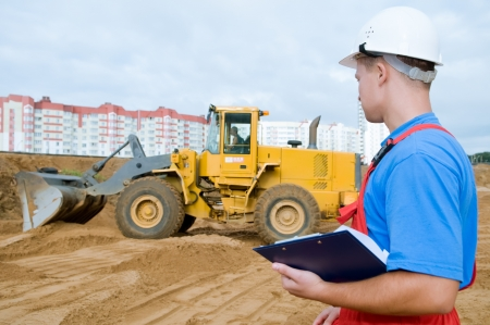 taskmaster: One builder worker with clipboard inspecting earthmoving works at construction site. Focus on worker Stock Photo