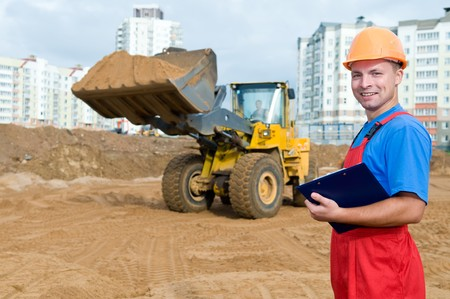 One builder worker with clipboard inspecting earthmoving works at construction site photo