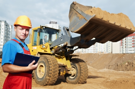 One happy builder worker with clipboard inspecting earthmoving works at construction site photo