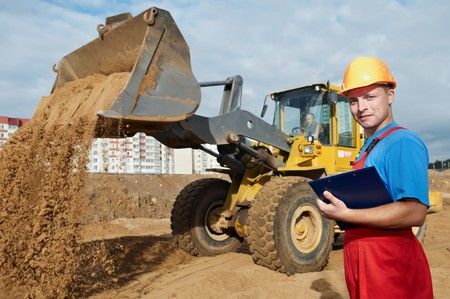 One happy builder worker with clipboard inspecting construction site photo