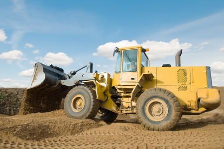 earthmover: Wheel loader machine unloading sand at eathmoving works in construction site