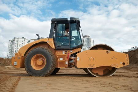 construction vibroroller: soil vibration roller during sand compacting works at construction site