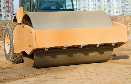compacting: soil vibration roller during sand compacting works at construction road site