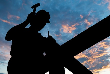 worker silhouette with hammer at roofing works over scenic dawn or sunset photo