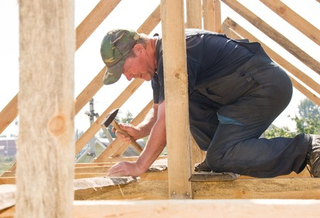builder worker nailing with hammer at roofing construction works photo