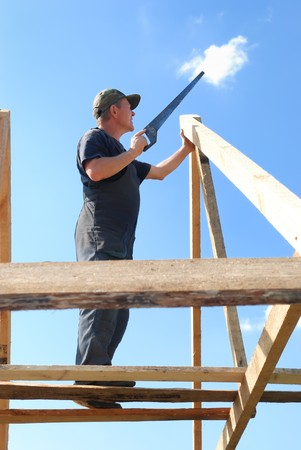 worker builder at roofing works over blue sky photo