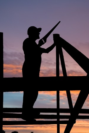 worker silhouette at roofing works over scenic dawn or sunset photo