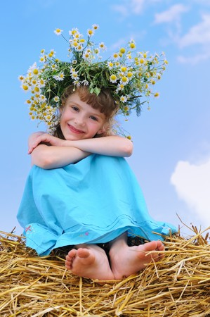 Happy smiley girl with camomile wreath outdoors over blue sky on straw haystack photo