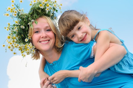 Happy mother with camomile wreath and daughter in summer over blue sky photo