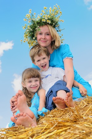 Happy mother with children in summer at field and straw haystack photo