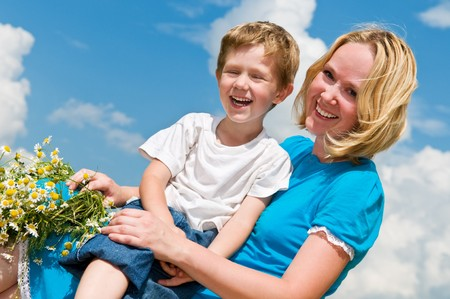 Happy mother with camomile wreath and son in summer over blue sky Stock Photo - 7818004