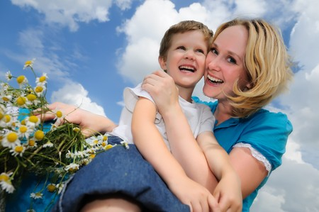 Happy mother with son in summer at field and straw haystack photo