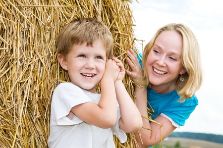Happy playing mother with son in summer at field and straw haystack Stock Photo - 7818013