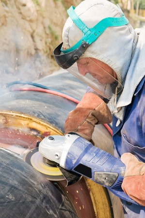 Builder works with circular abrasive cutoff saw grinding machine and sparkles at construction site photo