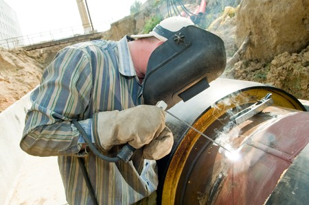 electrode: welder works with electrode in protective helmet and gloves Stock Photo